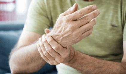 Homem segurando o pulso com dor causado pela artrite