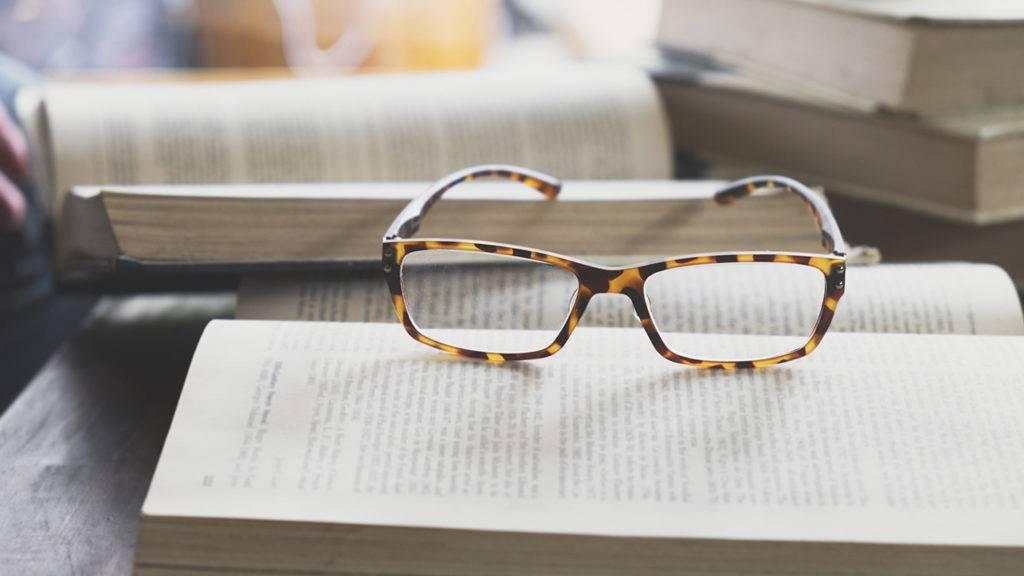 óculos colocados sobre um livro, mais livros aos fundo.
