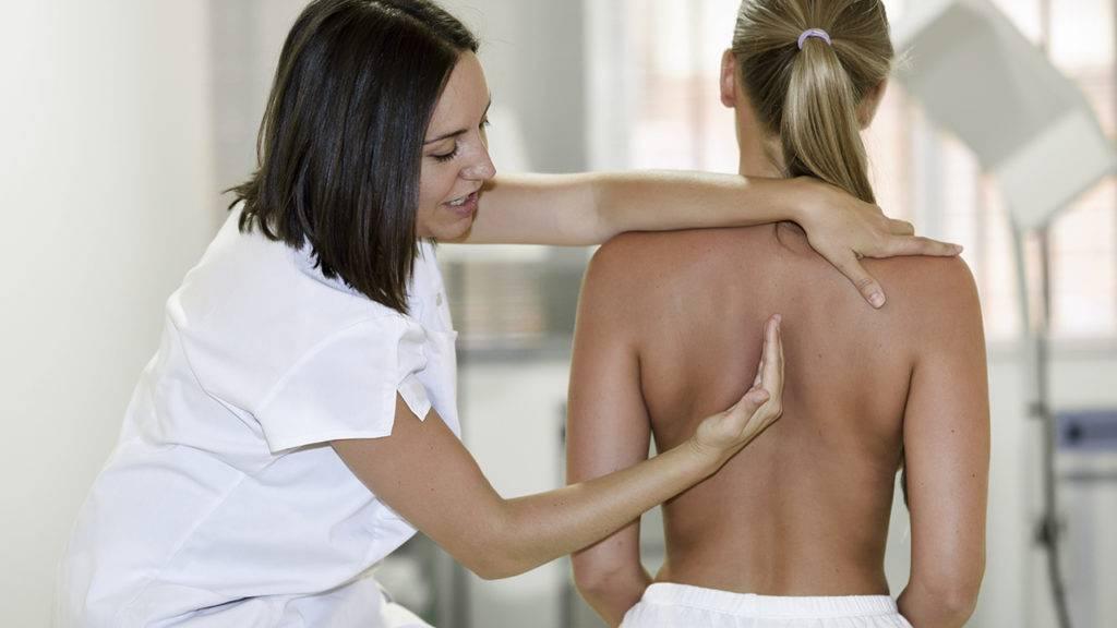 Doutora indicando a localização da coluna vertebral para a paciente.