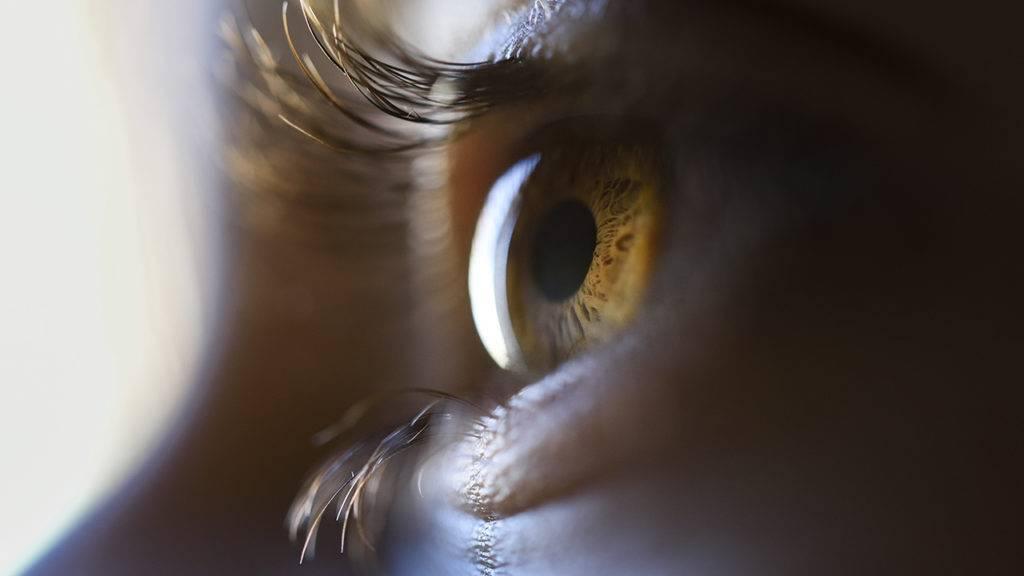 Foto super aproximada de um olho sob luz focal.