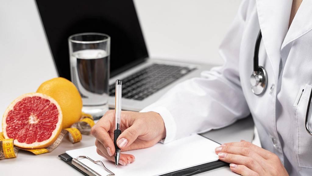 Nutricionista faz anotações em um papel, no fundo há uma grape fruit, um copo de água e um notebook.