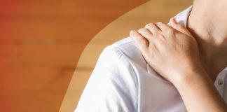 Mulher colocando a mão no ombro por causa da dor