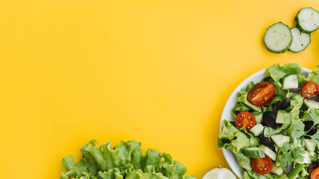 imagem com fundo amarelo e prato repleto de salada com alfaces, tomates, azeitonas e pepino.