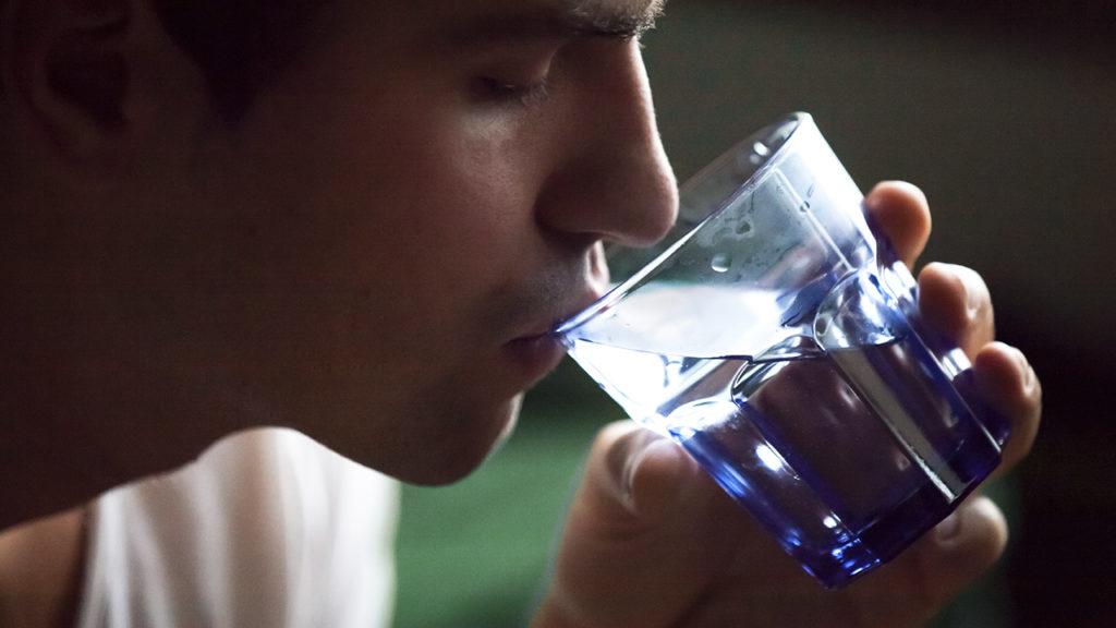 Homem bebendo água com muita sede por polidipsia.