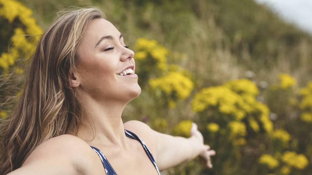 Mulher feliz e saudável de braços abertos na natureza.