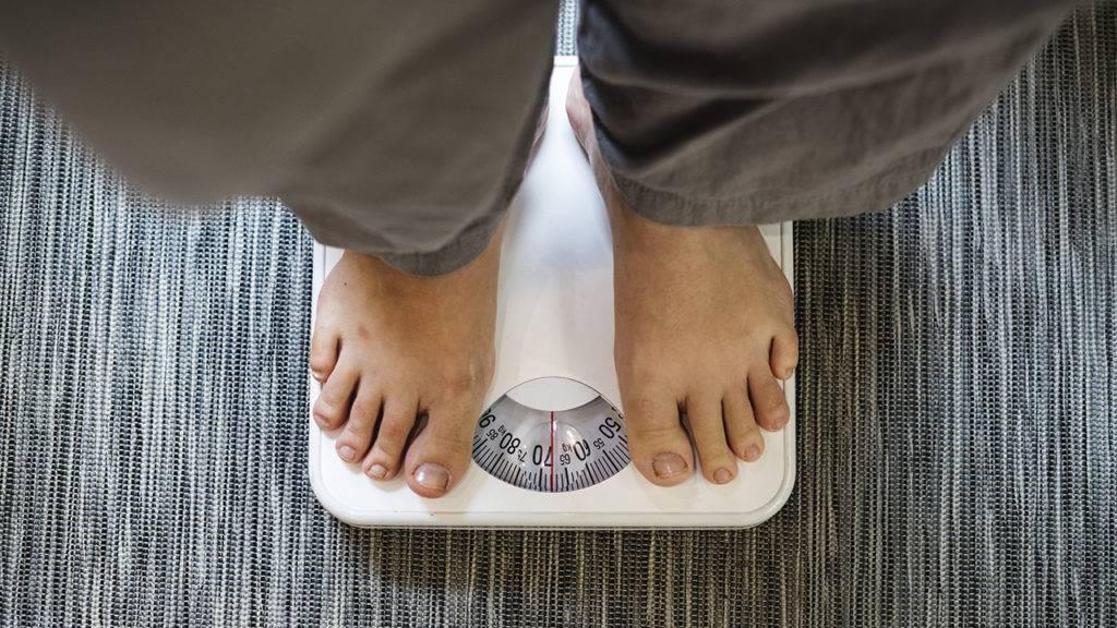 Mulher sobre uma balança pesando aproximadamente 70 kilos,