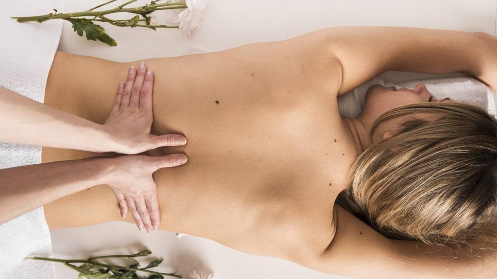 Mulher loira recebendo massagem.