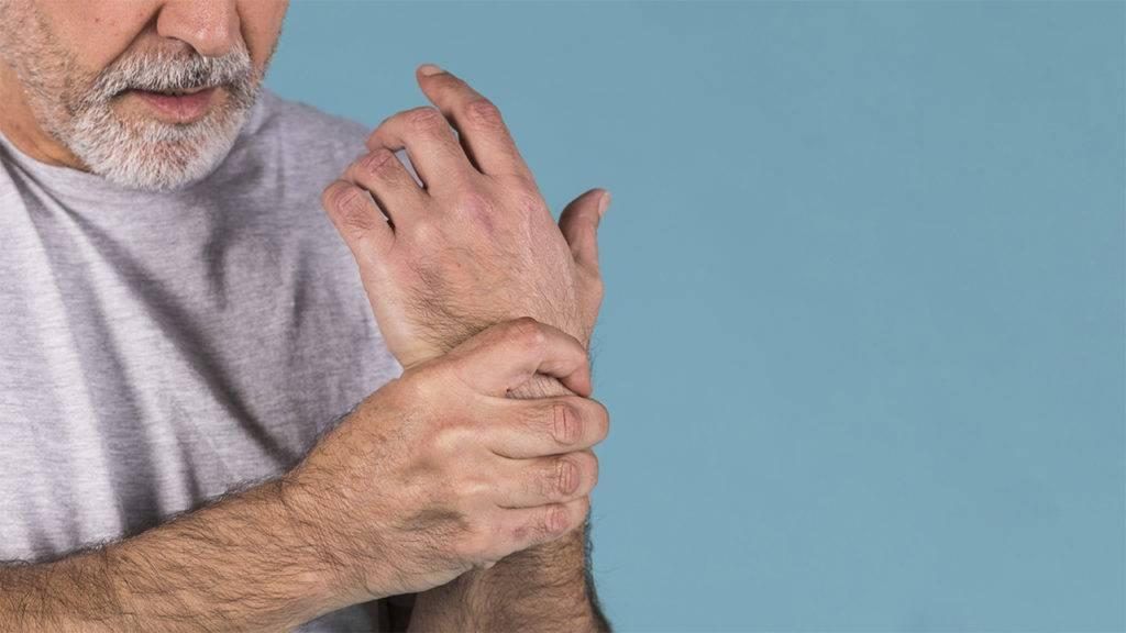 Idoso segurando o pulso com dor nas juntas por causa da artrite.