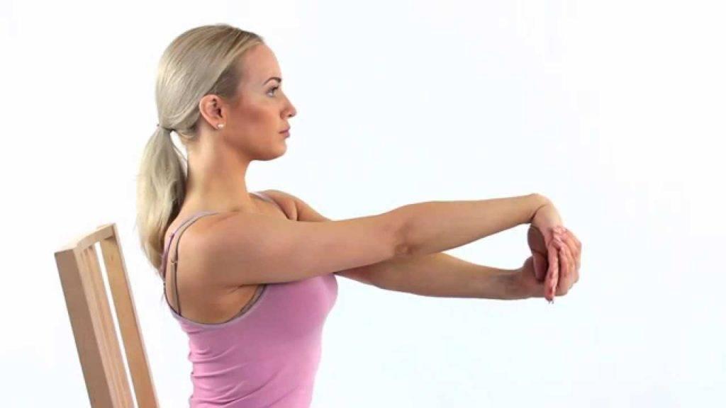 Mulher sentada em uma cadeira fazendo alongamento para o pulso com a palma da mão virada para dentro.